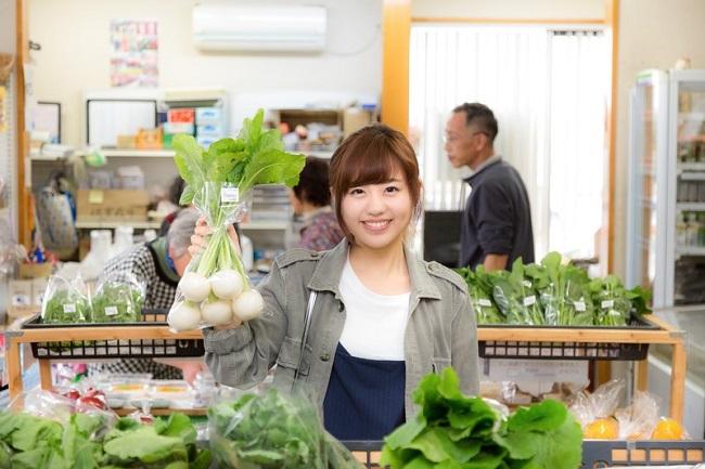 野菜を持ち上げる女性